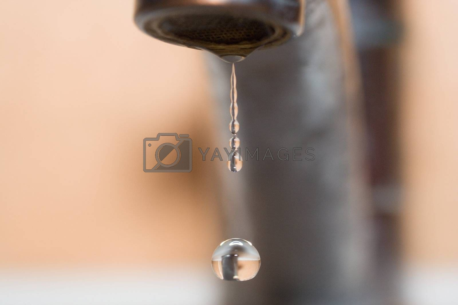 drop of water from faucet in bathroom with reflection