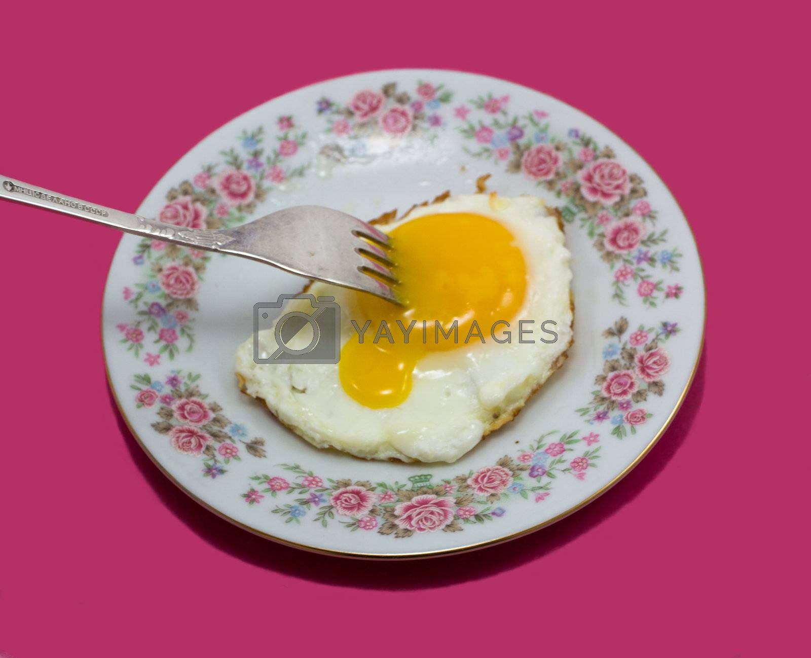 fried egg on plate with fork, isolated on purple background