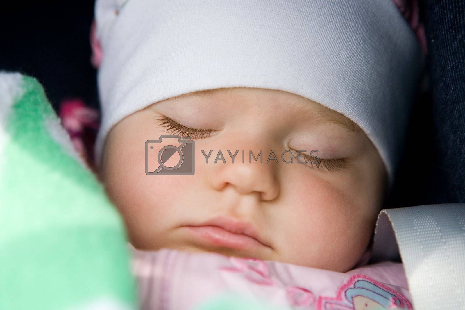 A portrait of the sleeping beautiful little girl in a white scarf close up