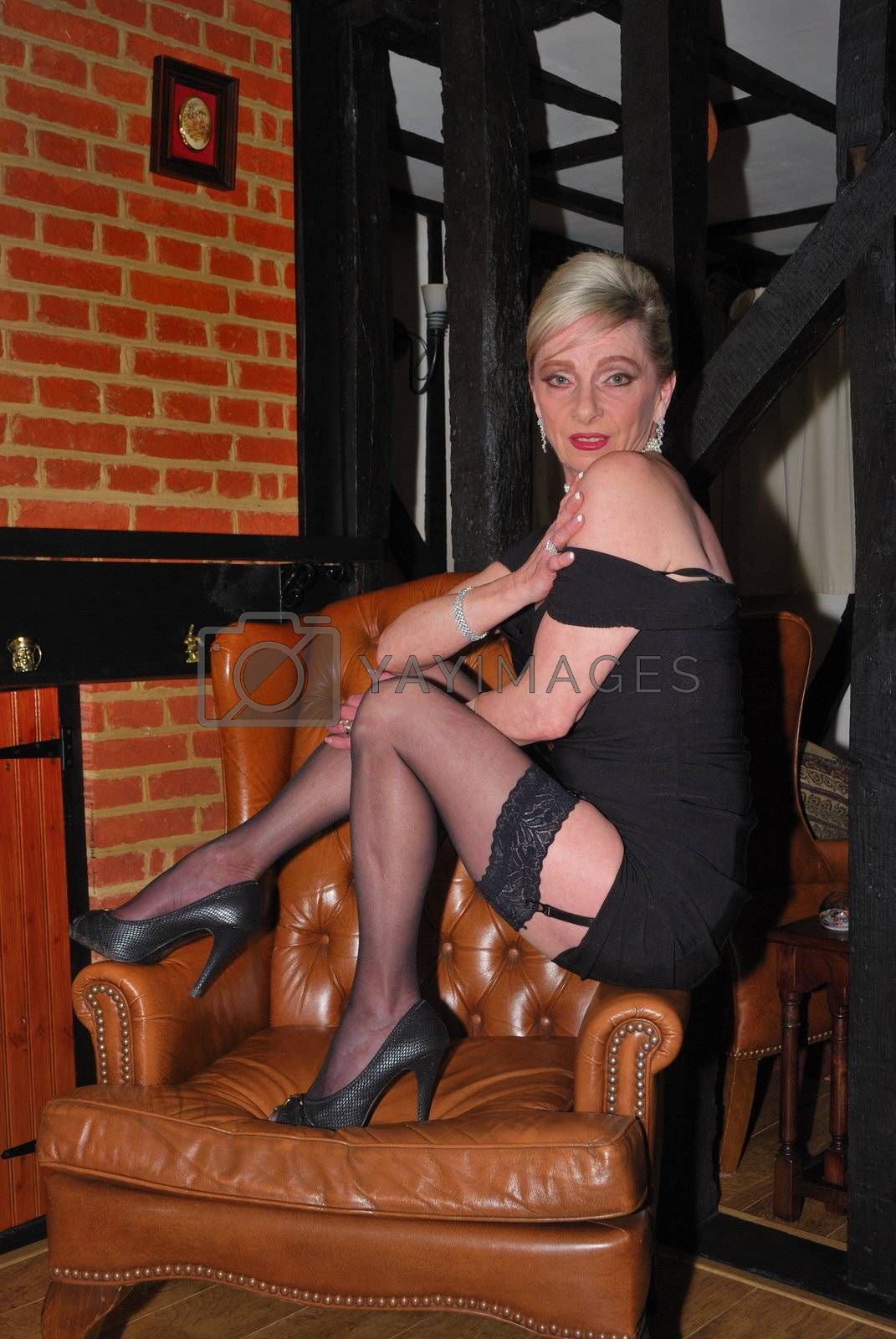 Older woman sitting on armchair seductively