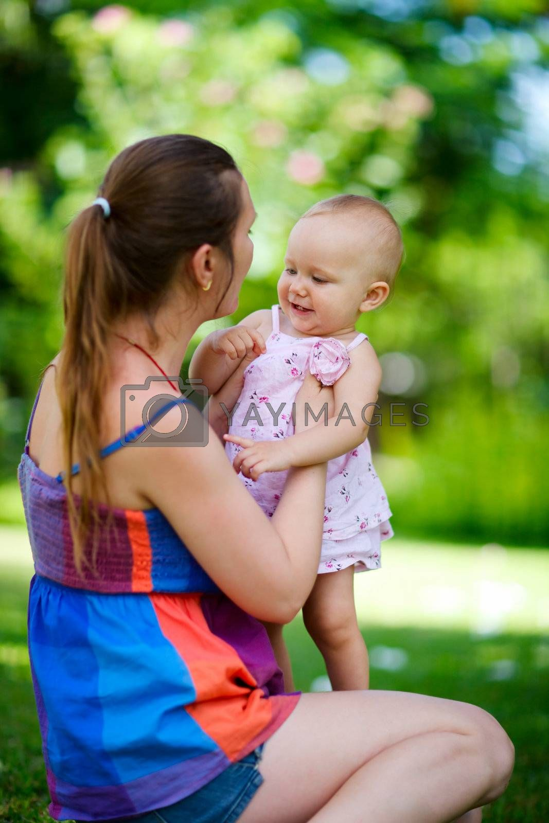 Lifestyle portrait of young mother and baby daughter outdoors