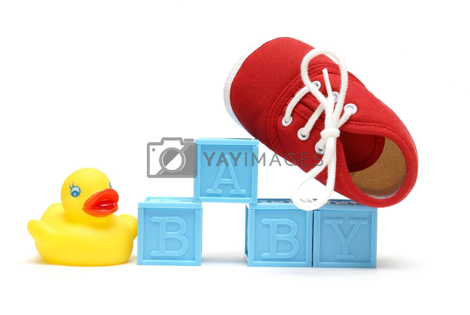 The word baby is isolated on white with a rubber ducky and a red shoe.