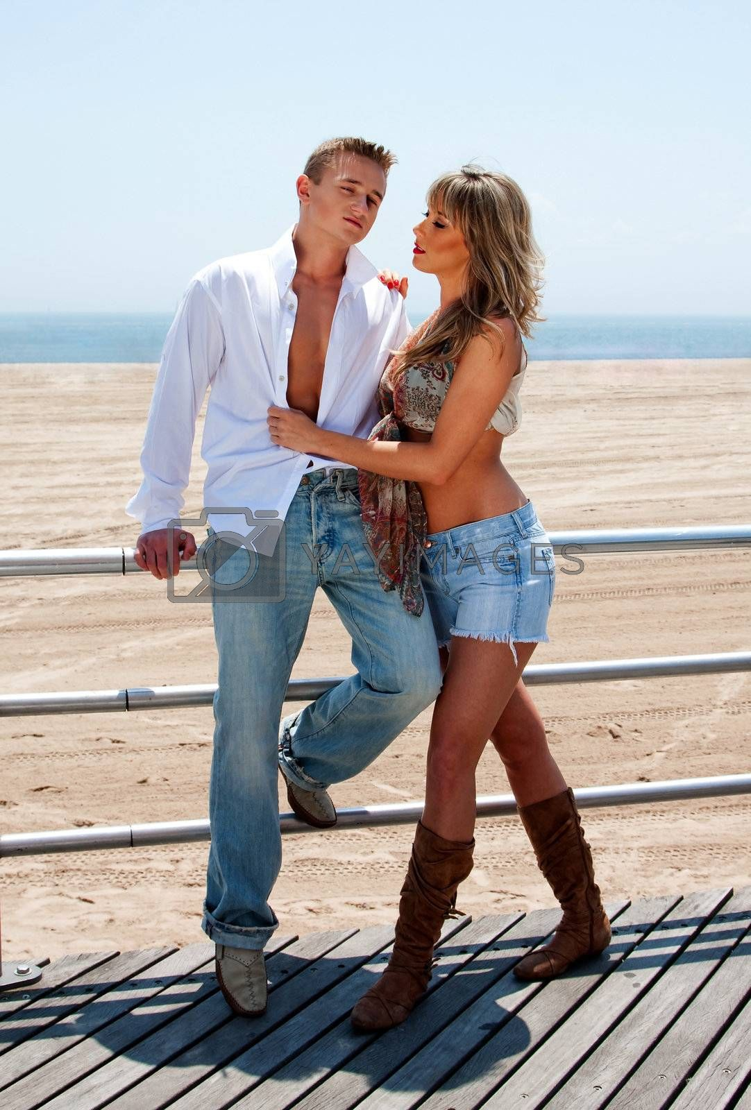 Young sexy couple, man and woman, next to railing on the boardwalk at the beach standing romantically together