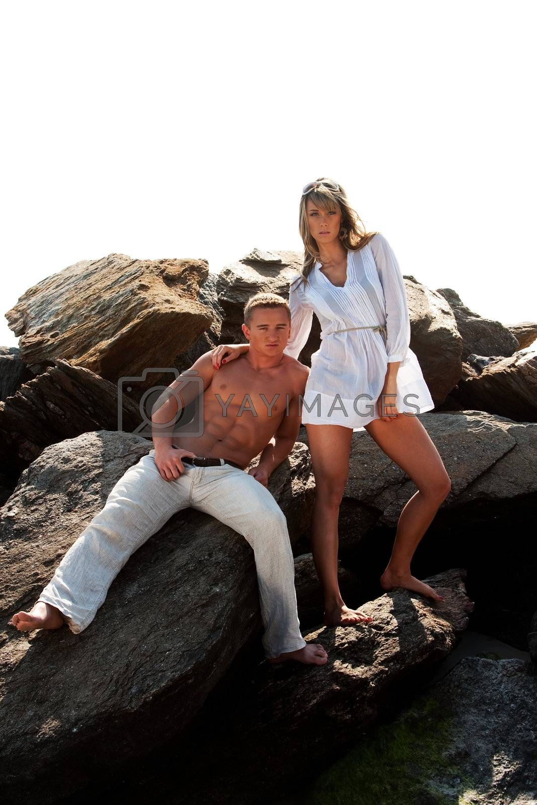 Caucasian guy and girl together on rock formation. Female is wearing long white shirt and holding sunglasses, standing on rocks. Guy showing muscular abs and bare torso wearing beige pants, heaving cool attitude, sitting on rocks. Together hanging out.