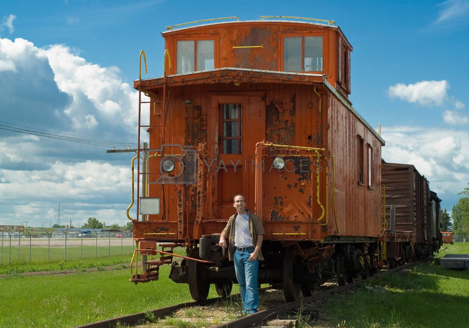 A train caboose shot on a partly cloudy day along with a young man to show the size of it
