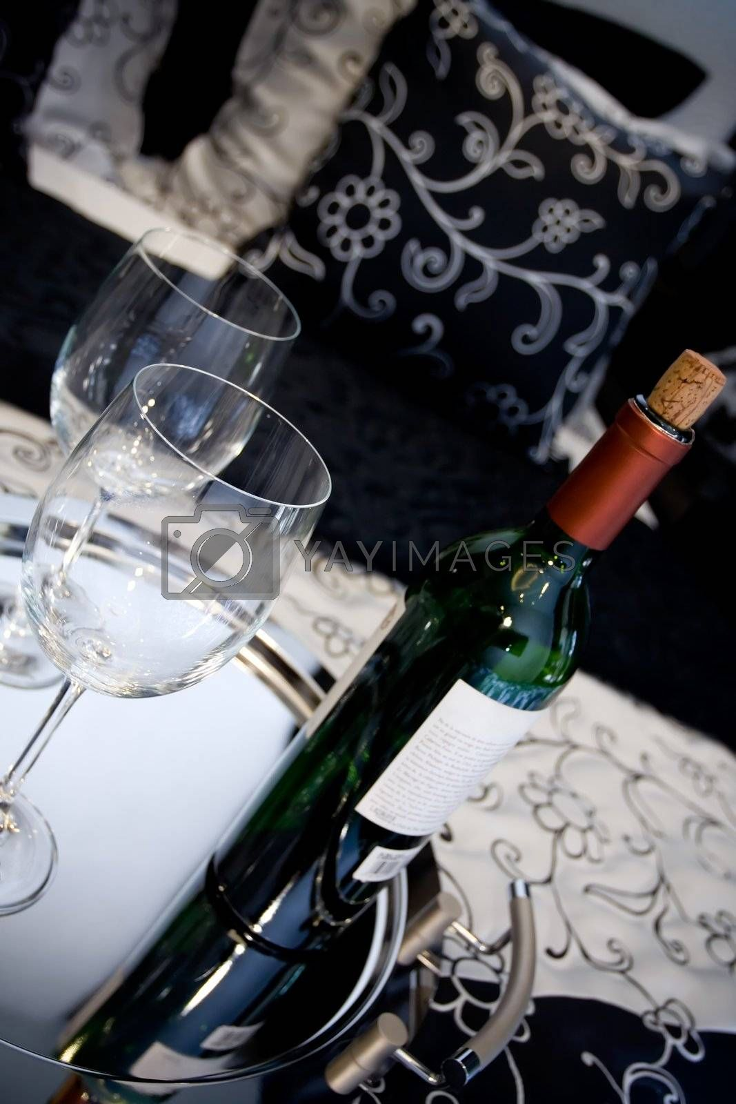 conceptual image of a bottle of wine and two glasses on the bed