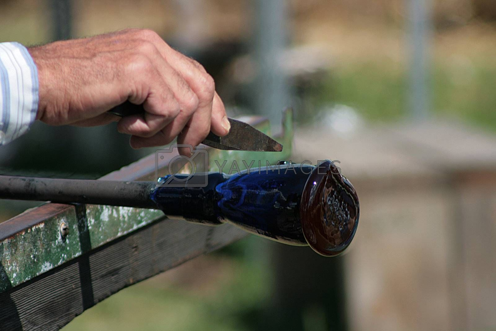 Glass-blower works over a new vase.