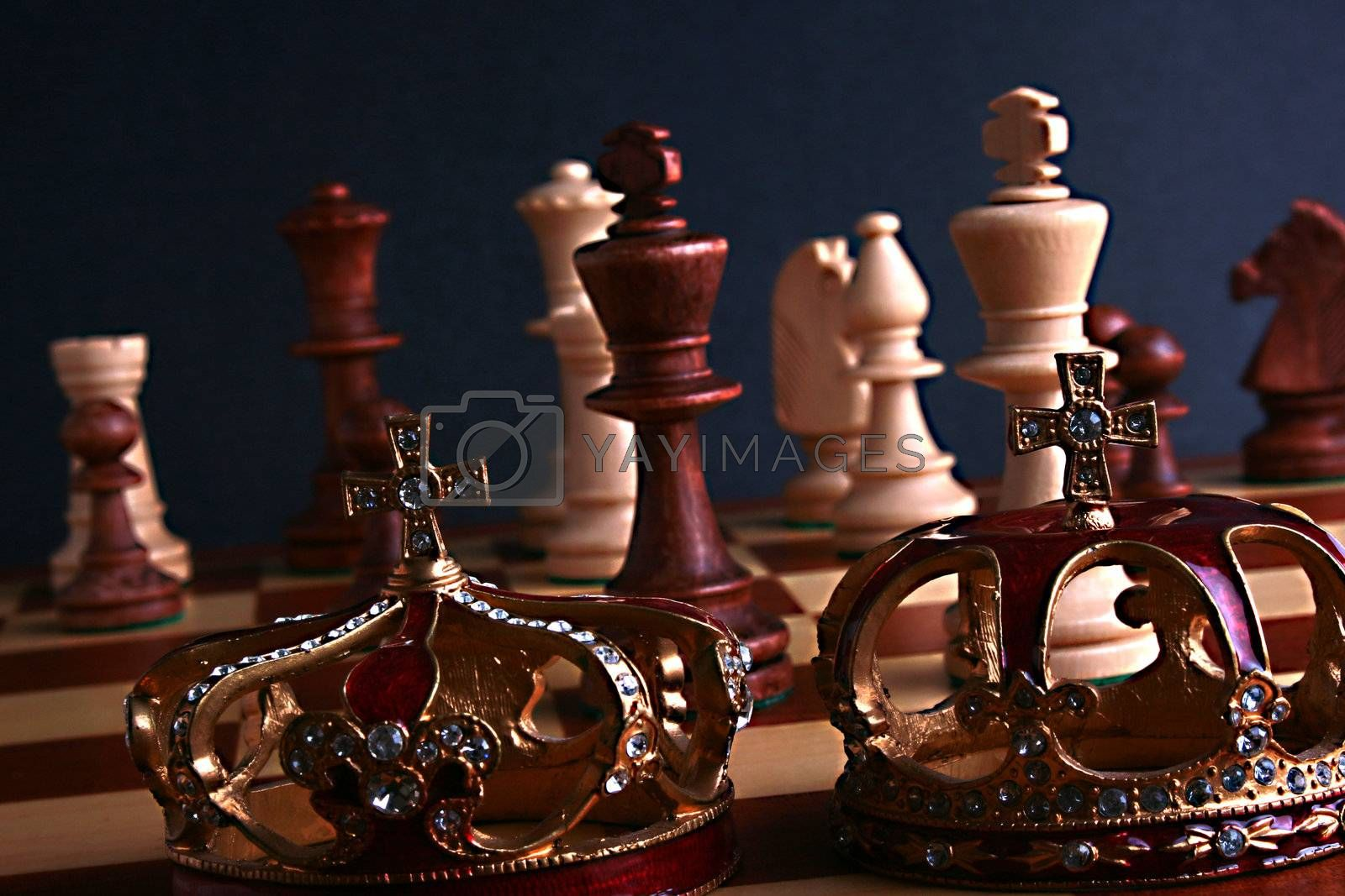 Chessmen on a game board with two crowns.