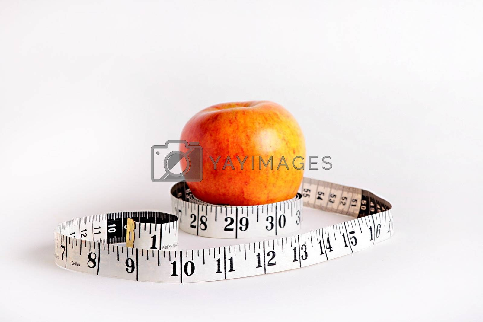 Tape measure and an apple characterise diet possibility.