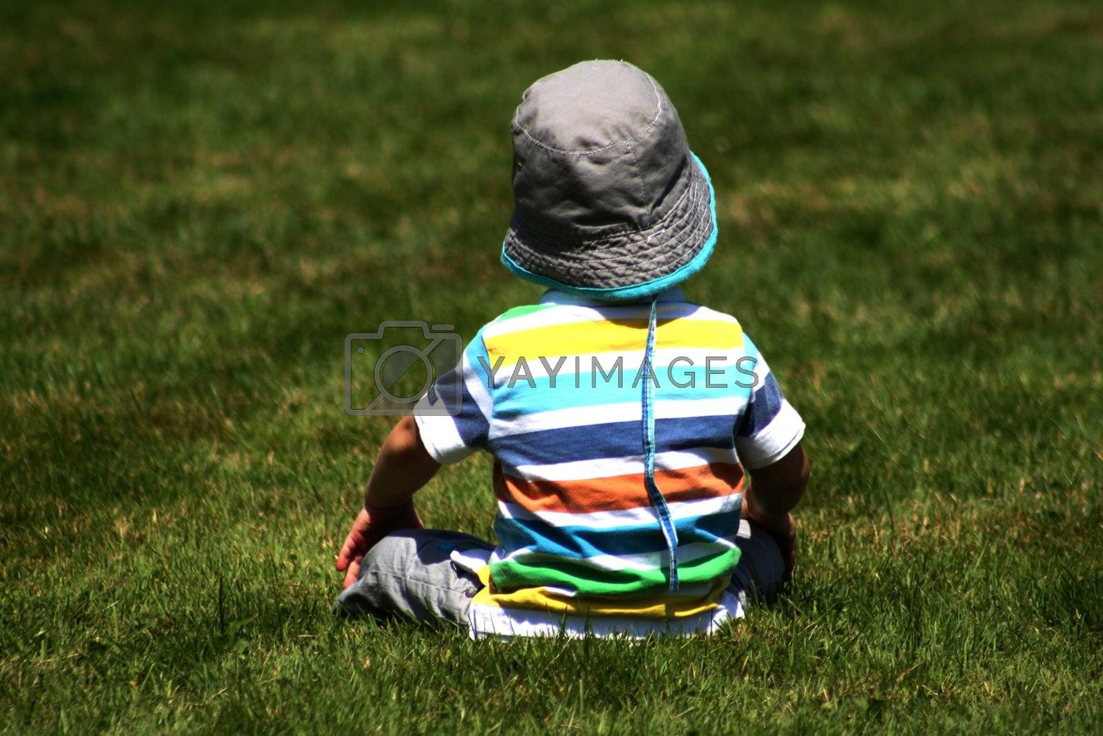 Toddler enjoying the sun while sitting in the grass
