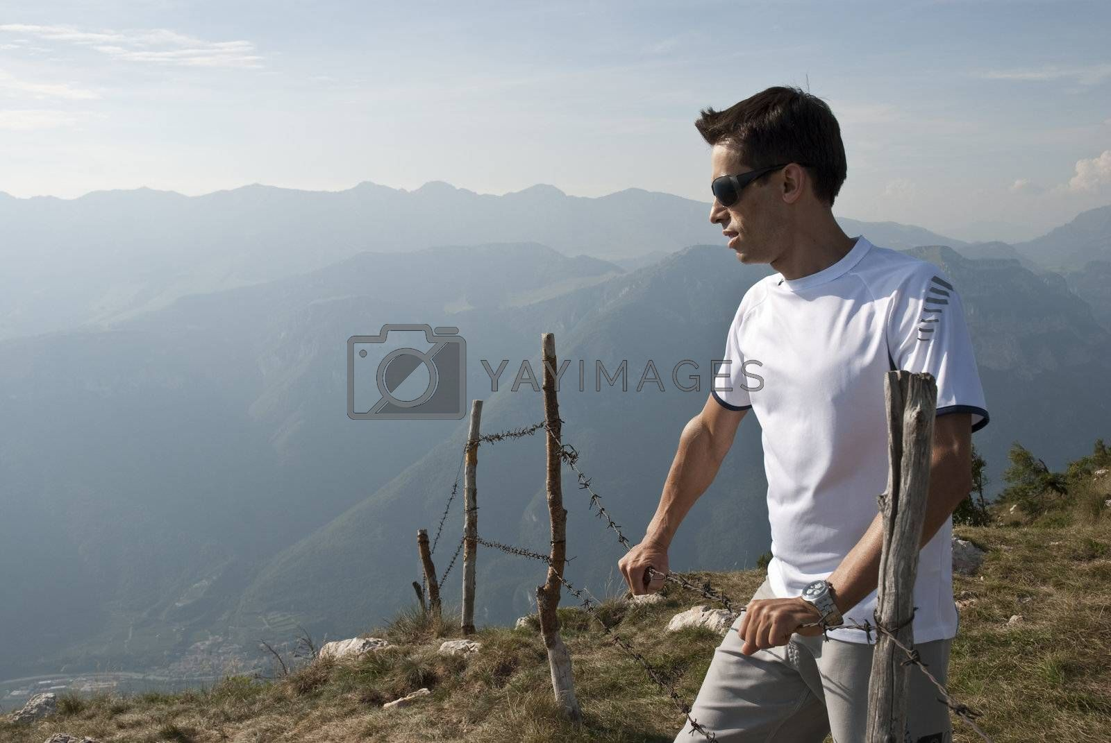 Young man against mountain background in a countryside hiking style scenary.