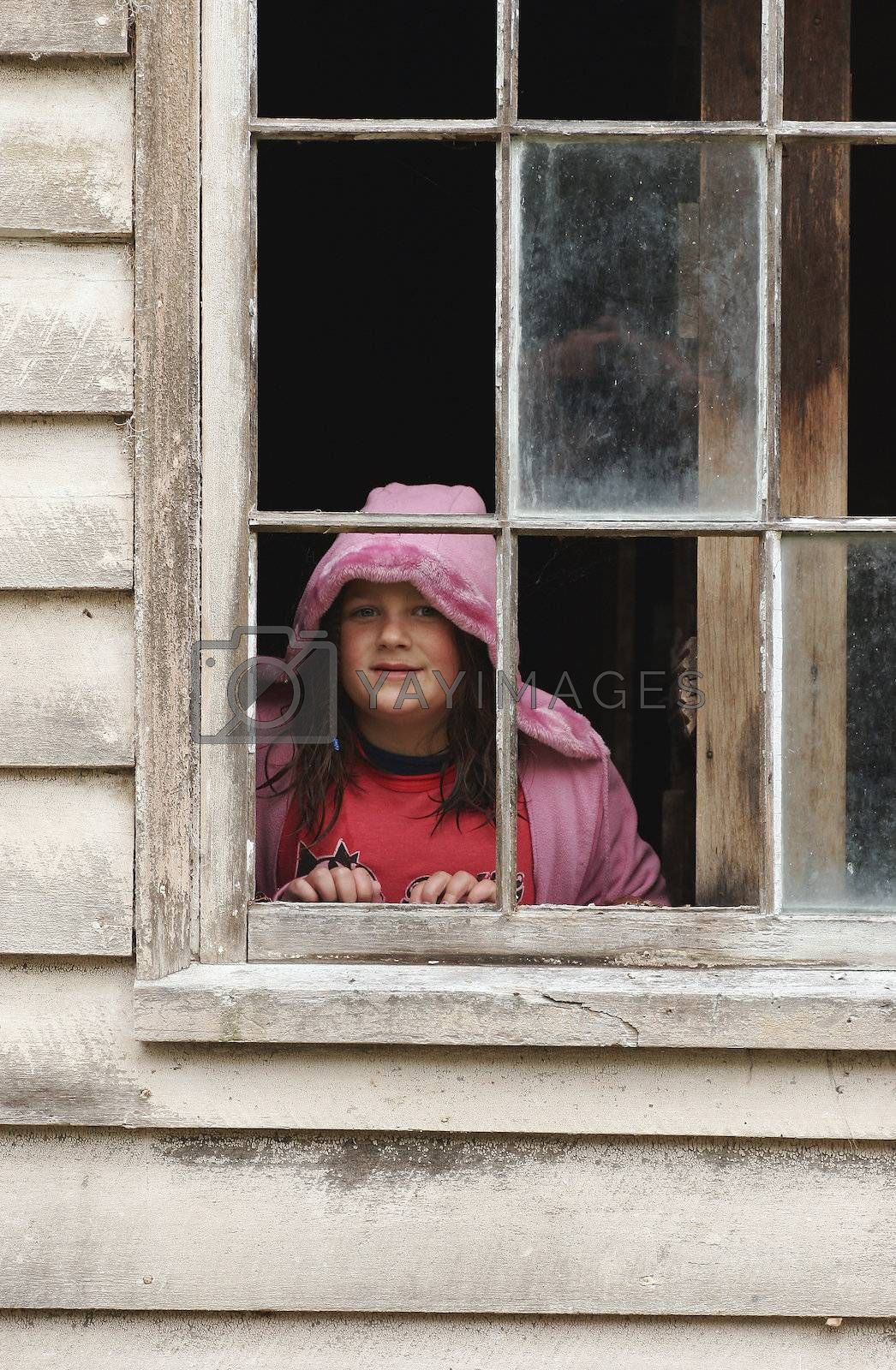 A girl looks out an old shed window