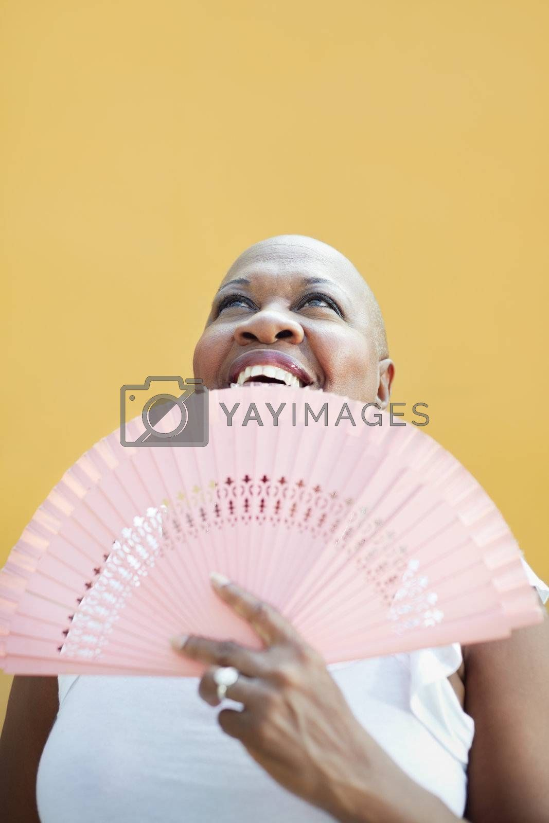 portrait of african 50 years old woman with bald head smiling on yellow background and looking up. Head and shoulders, copy space