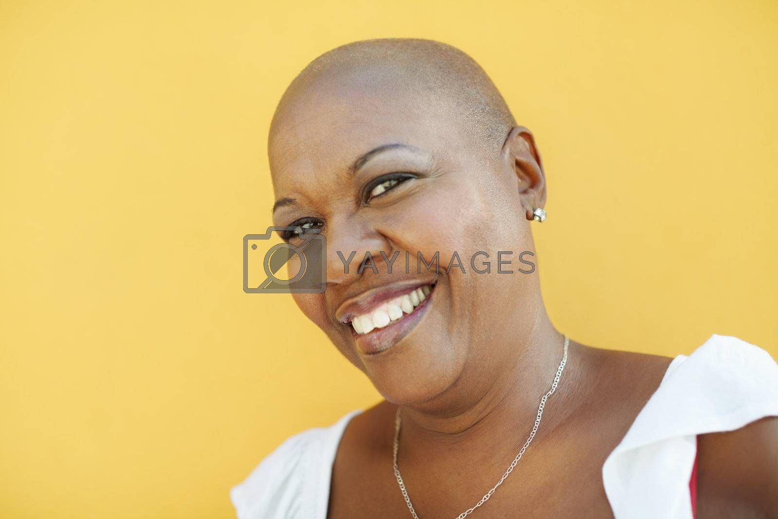 portrait of african 50 years old woman with bald head smiling at camera on yellow background. Head and shoulders, copy space