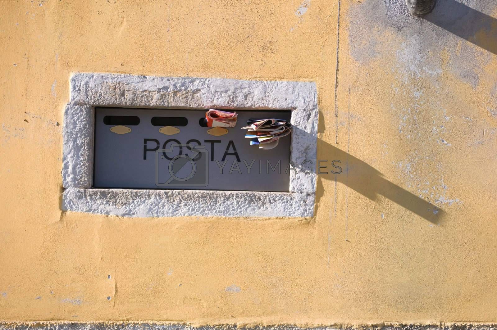Italian mailbox in yellow wall with newspapers