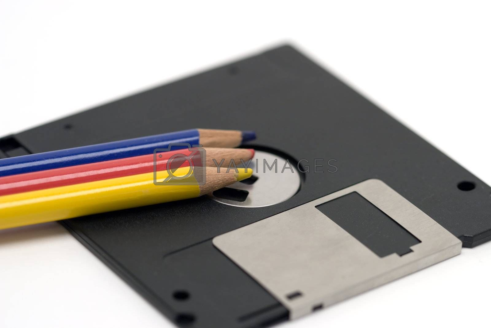 "Colored pencils and a 3.5"" floppy disk - examples of old technologies."