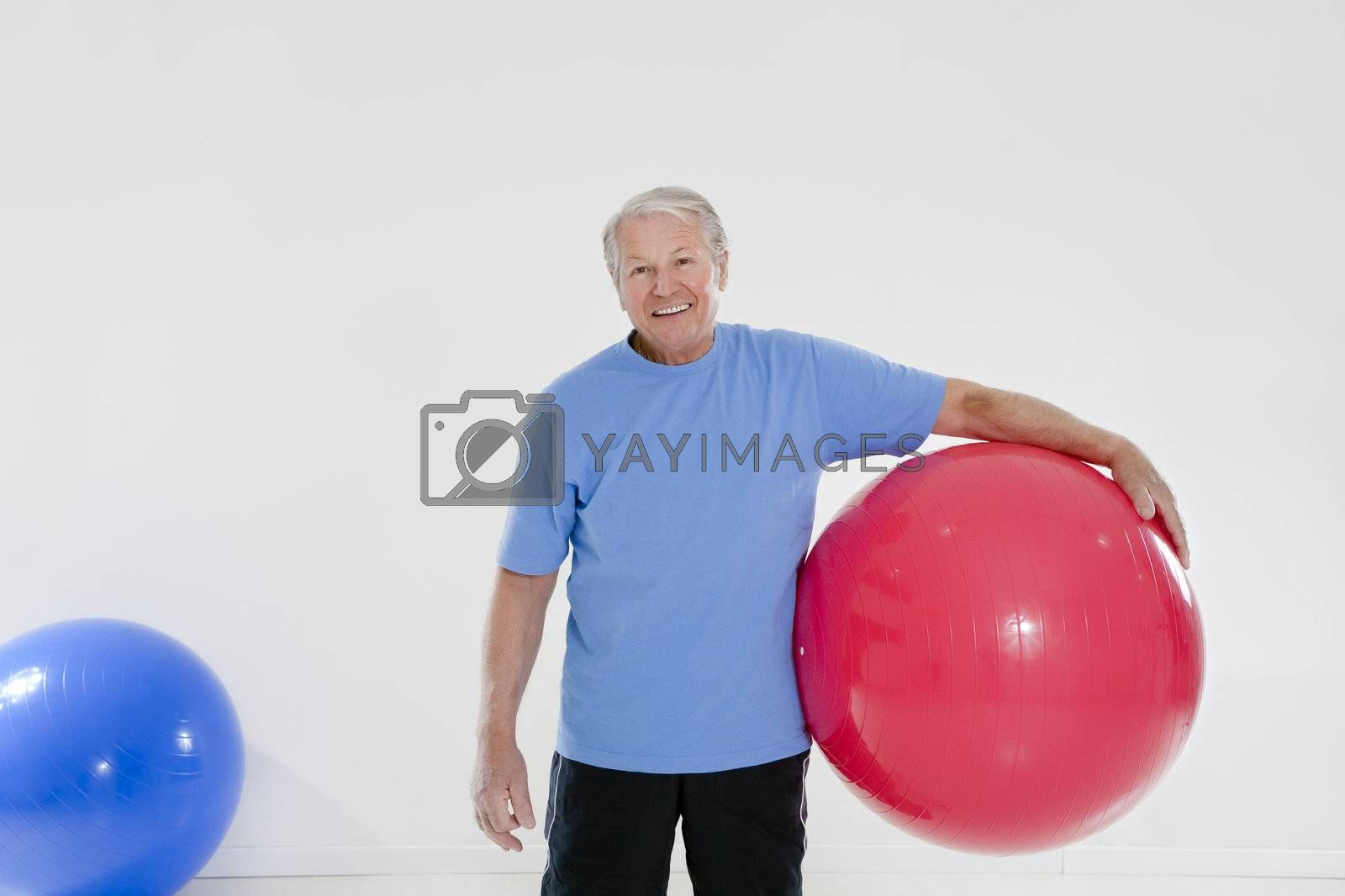 senior adult exercising with fitness ball in gym