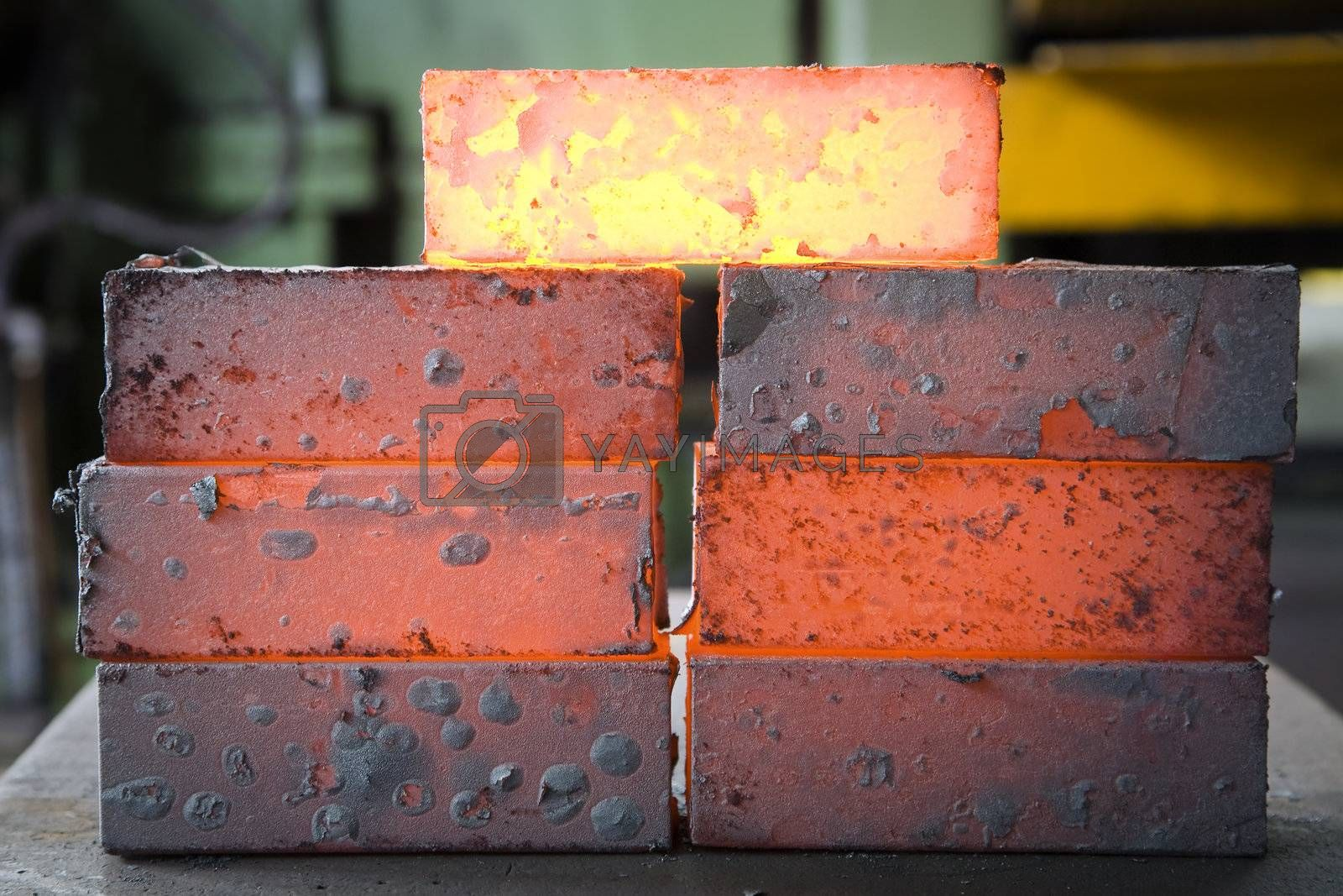 piles of hot iron blocks in foundry. Narrow focus on central block