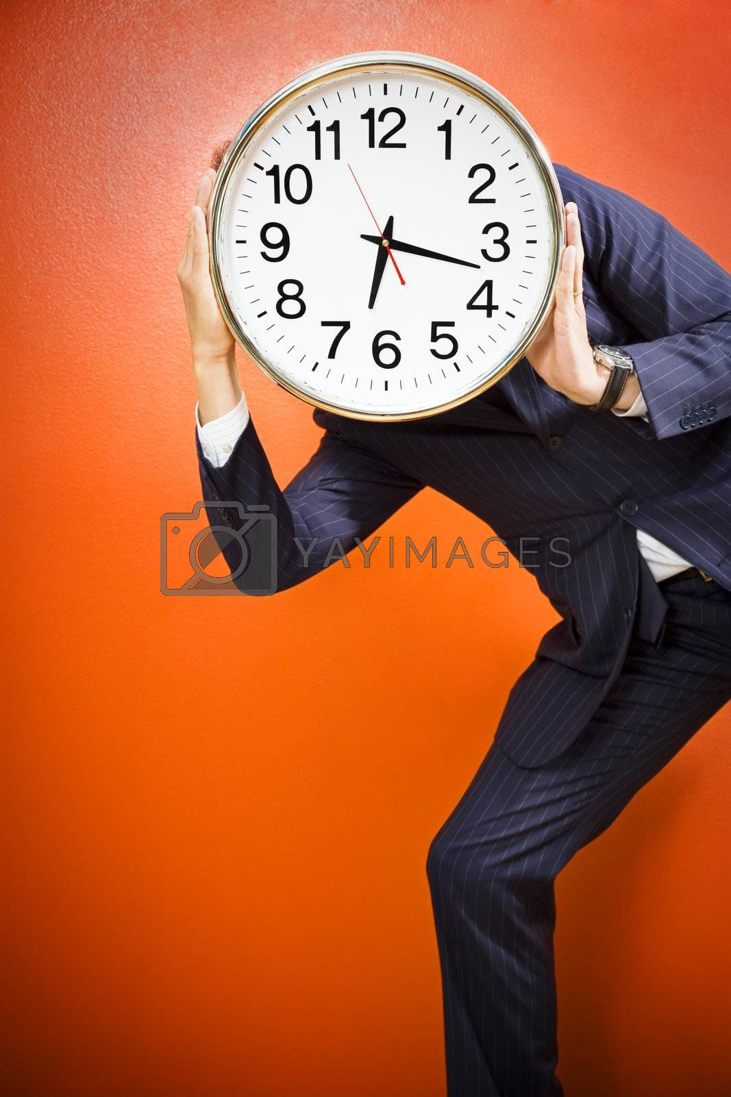 Businessman with clock on head, studio shot.