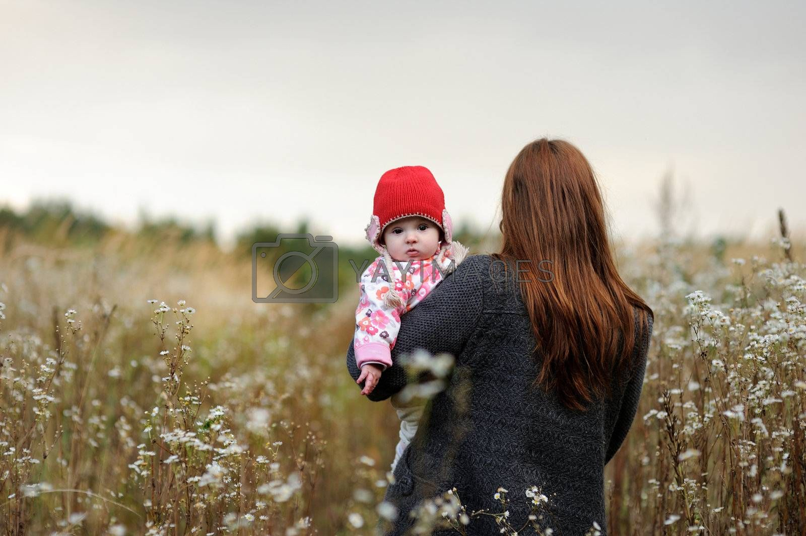 Young mother walking away holding her baby girl