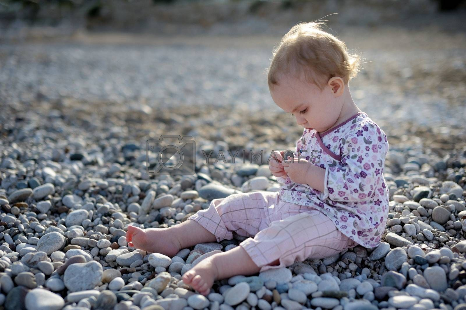 Little baby sitting by the sea on the stones and playing with them