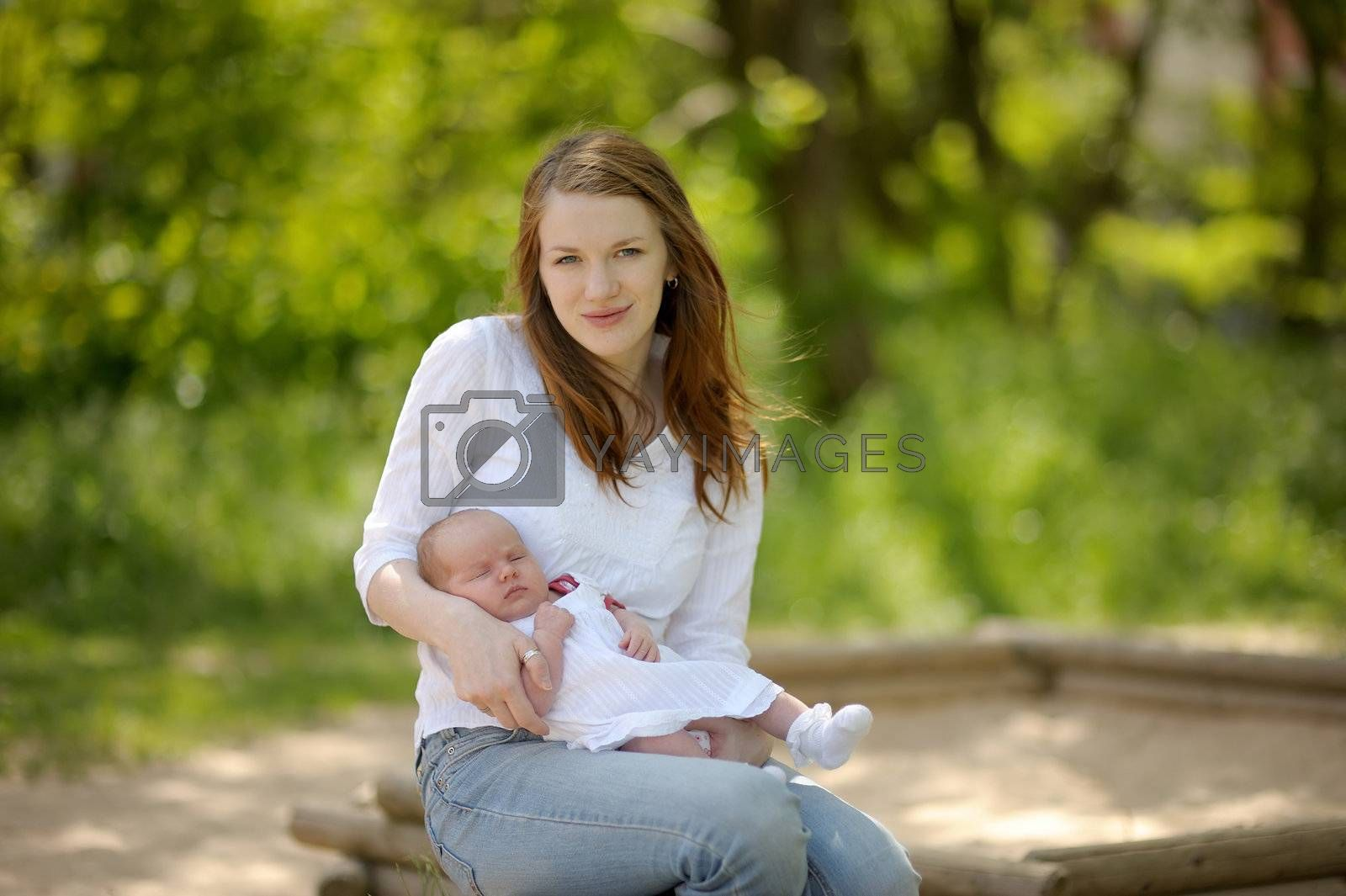 Young mother is holding her newborn baby in the arms