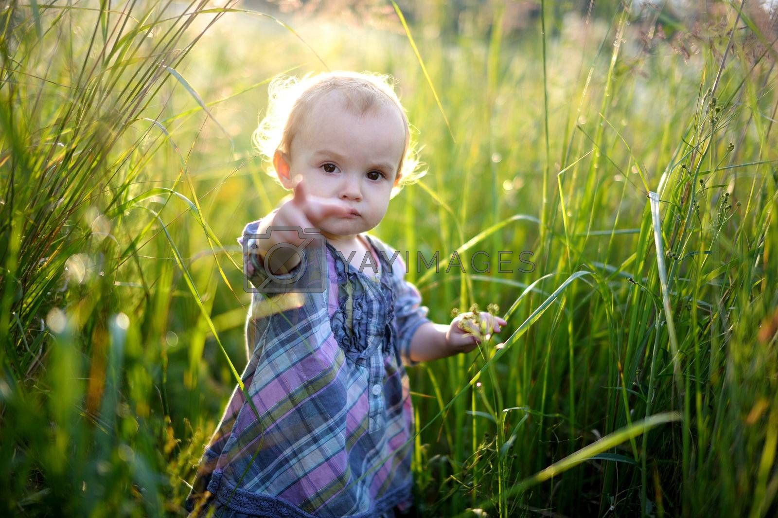 Little baby girl in an overgrown grass pointing with her finger at you with finger