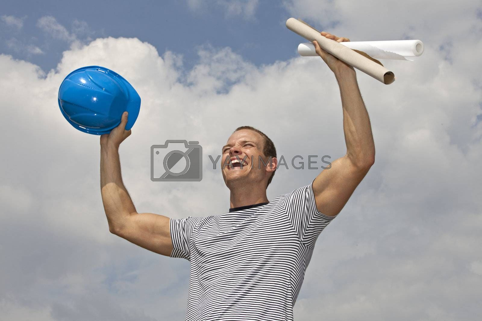 smiling young architect holding a hard hat and blueprints