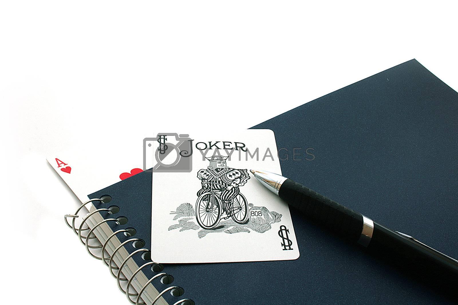 Card joker against a notebook. In a notebook an as.