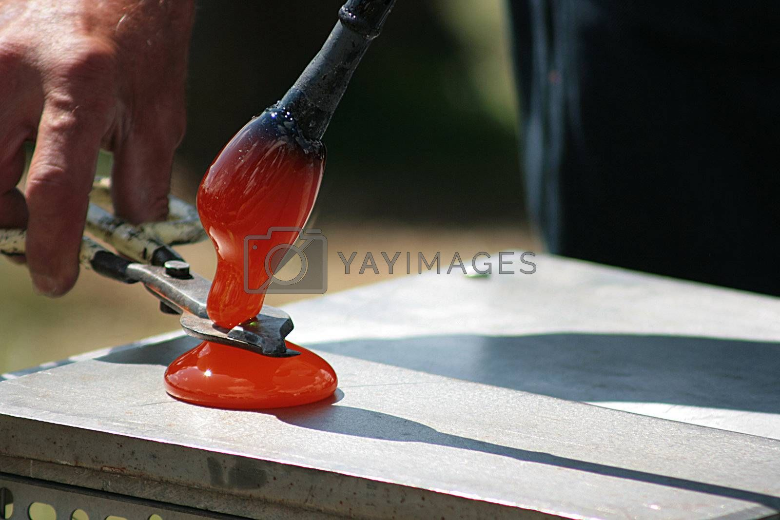 Glass blower works over a new vase.