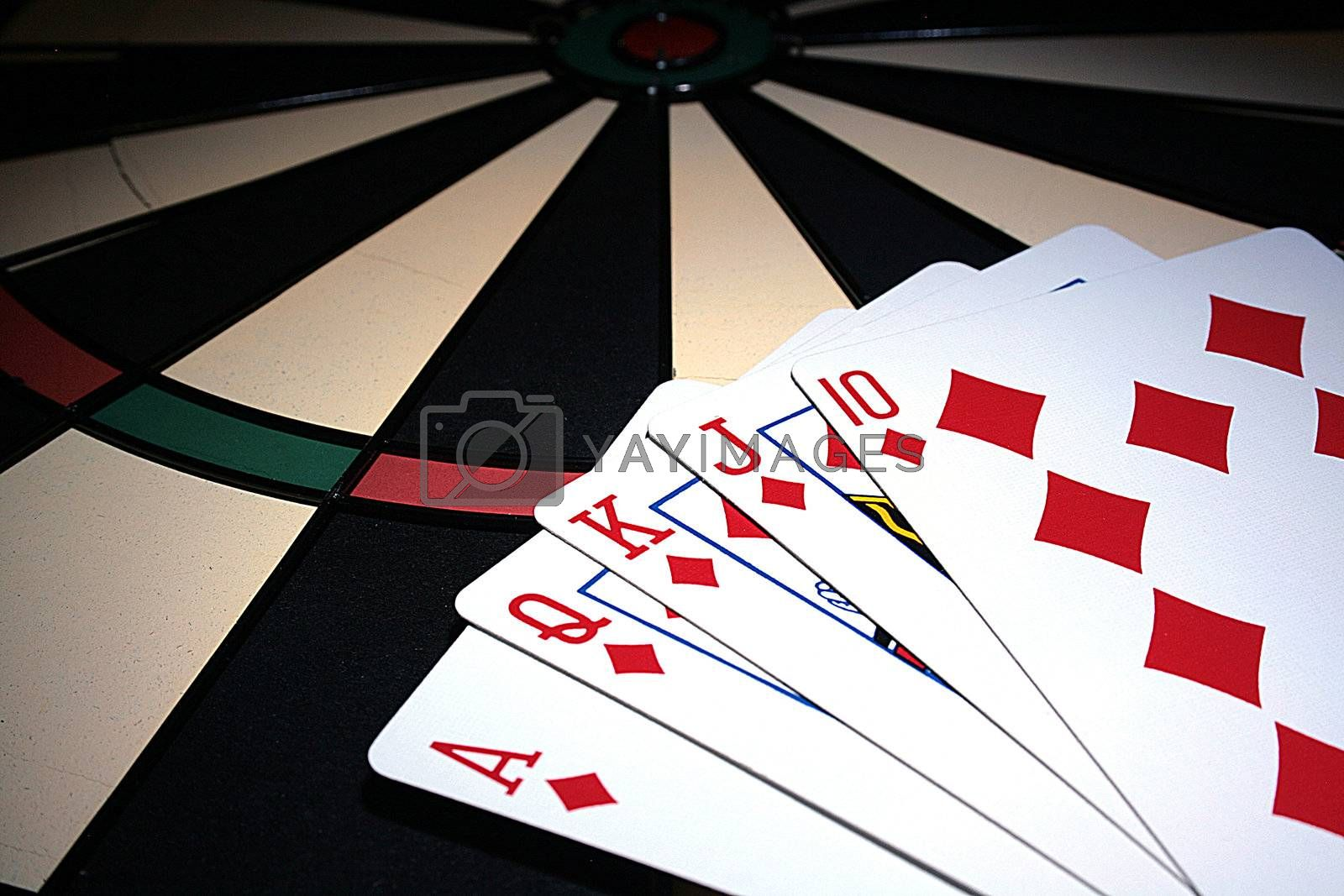 Playing cards on a board for game in a darts.