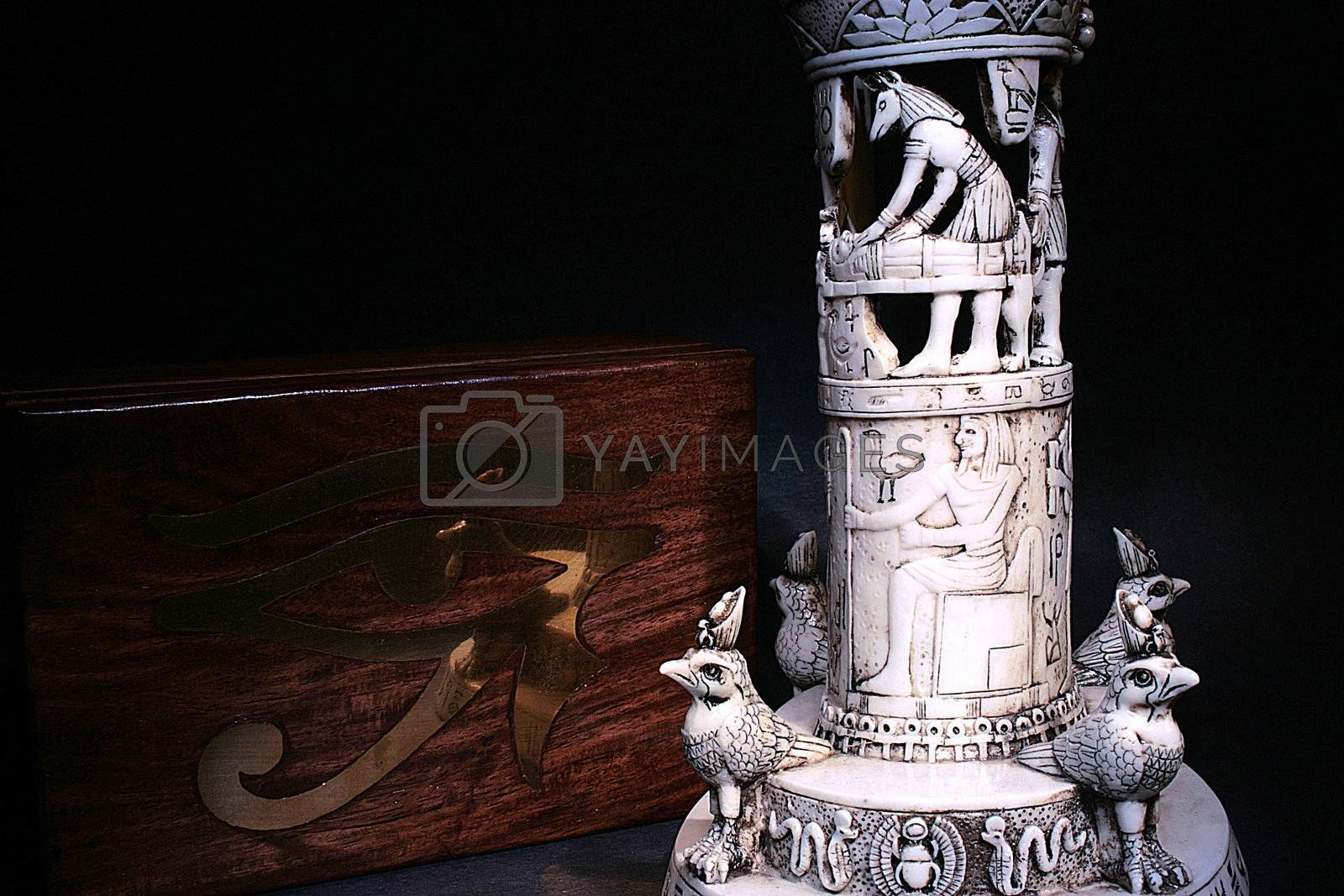 The Egyptian religious attributes: a casket with the Egyptian eye and a ritual column.