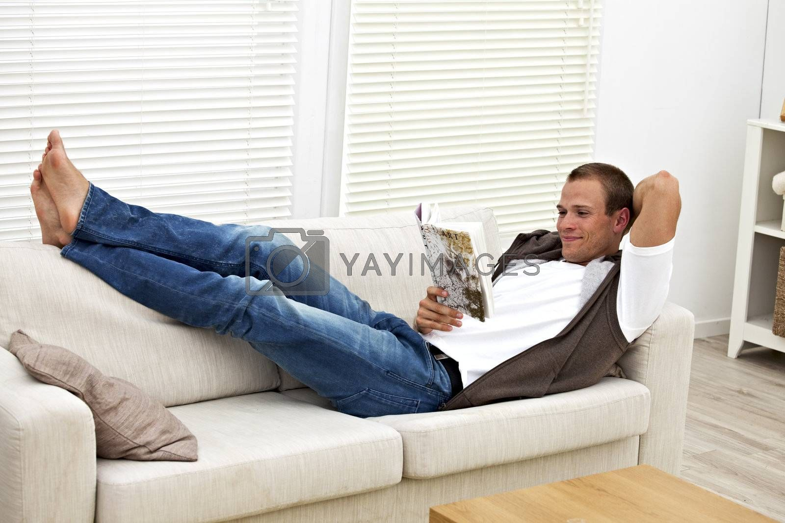 smiling young man on a couch reading a book