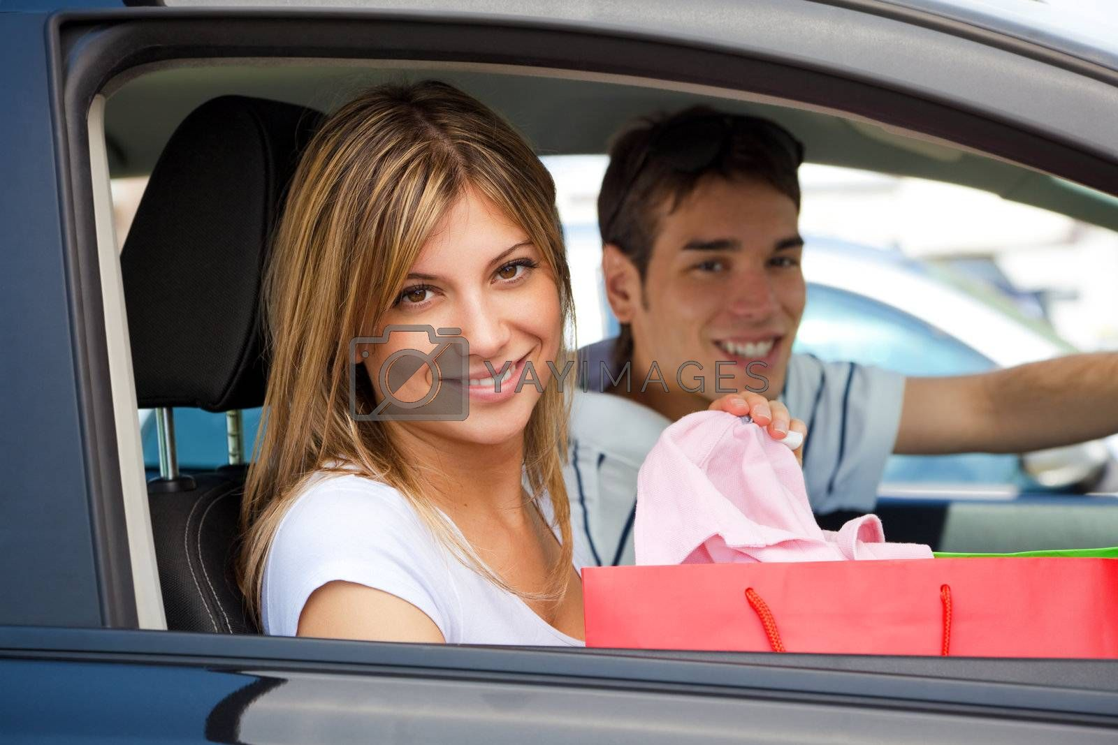 portrait of young couple in car after shopping