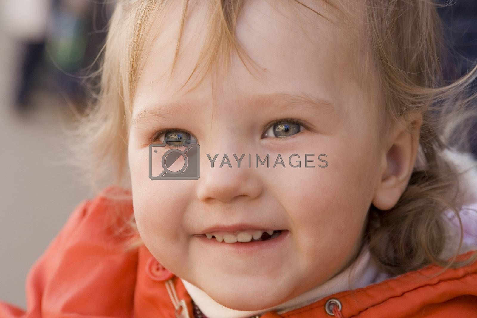 little smiling baby with curious eyes in orange