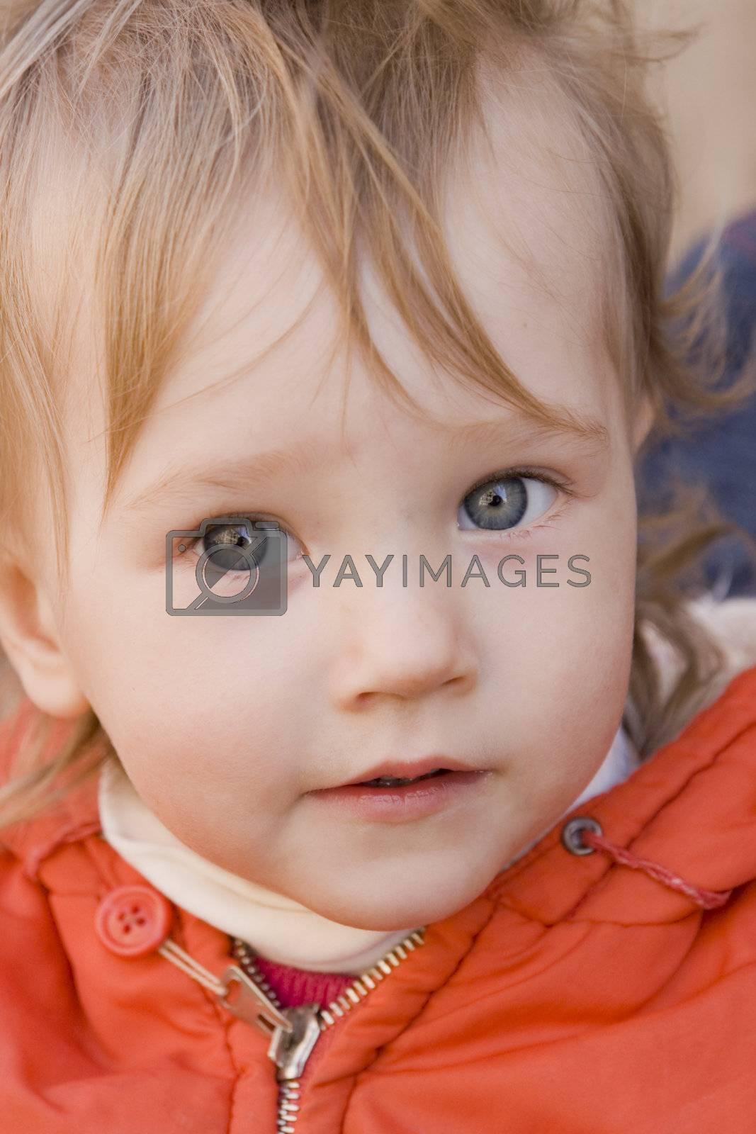 little girl wiyh curious eyes in orange dress