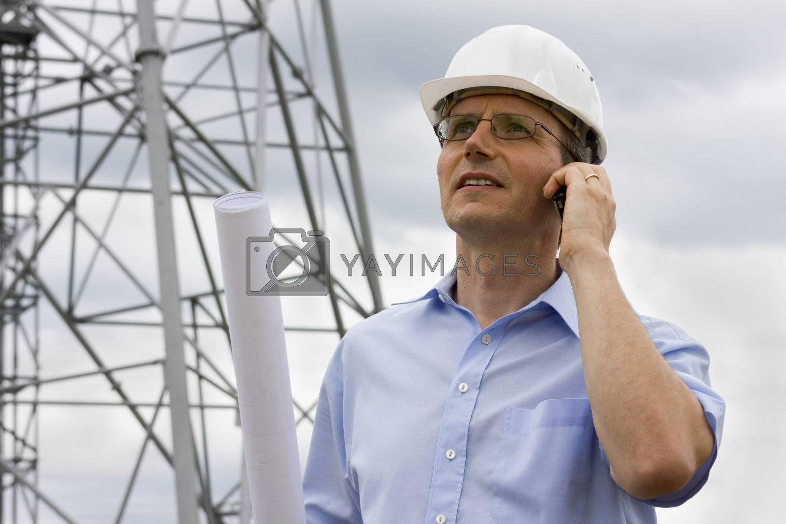 Engineer talking on mobile phone on construction side