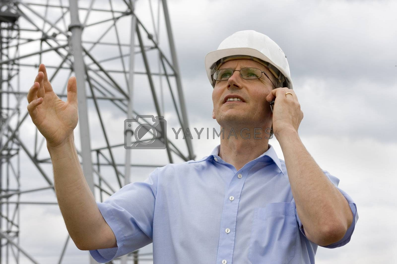 Engineer gesturing while talking on cell phone on construction side