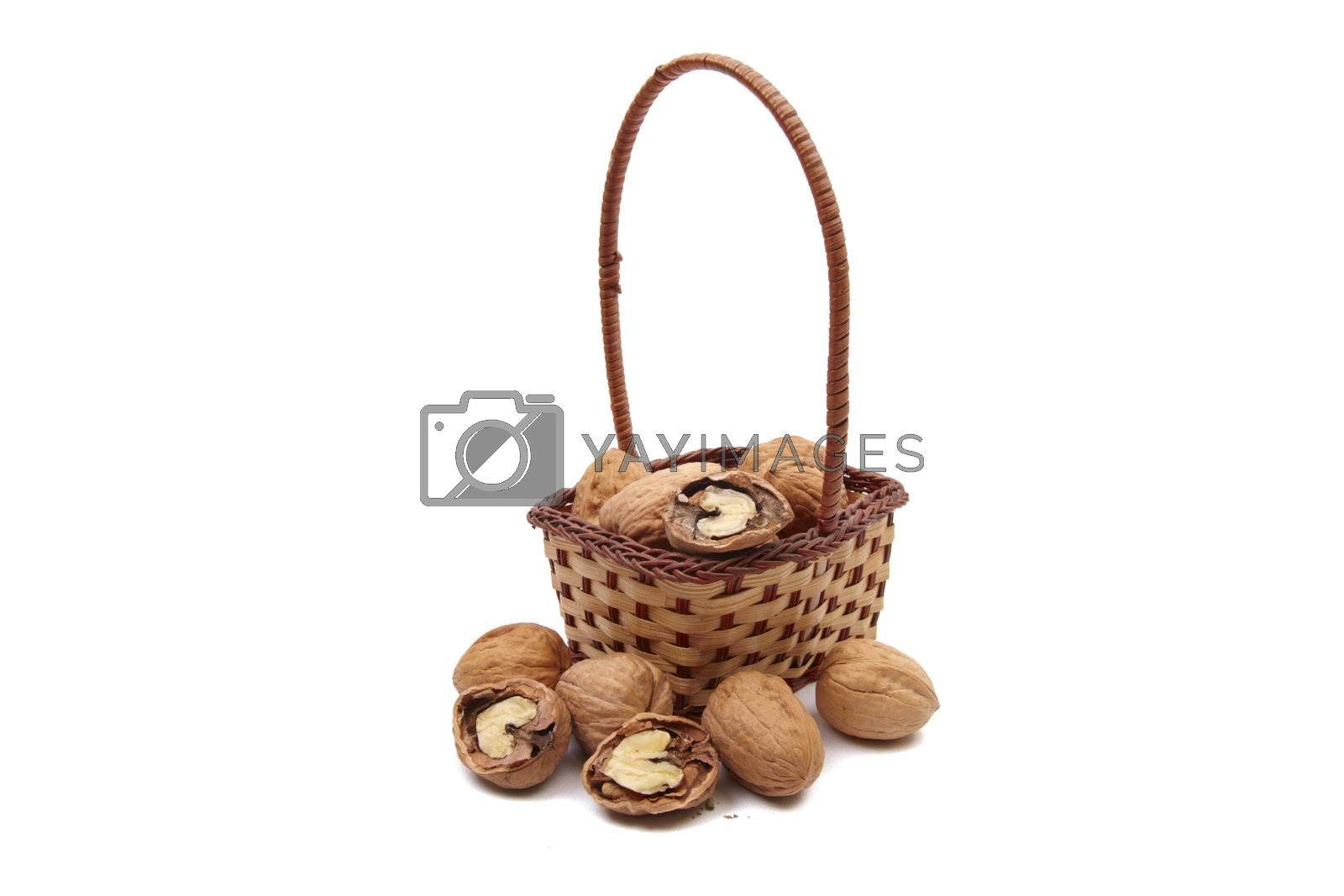 Walnuts in wicker basket isolated on white background