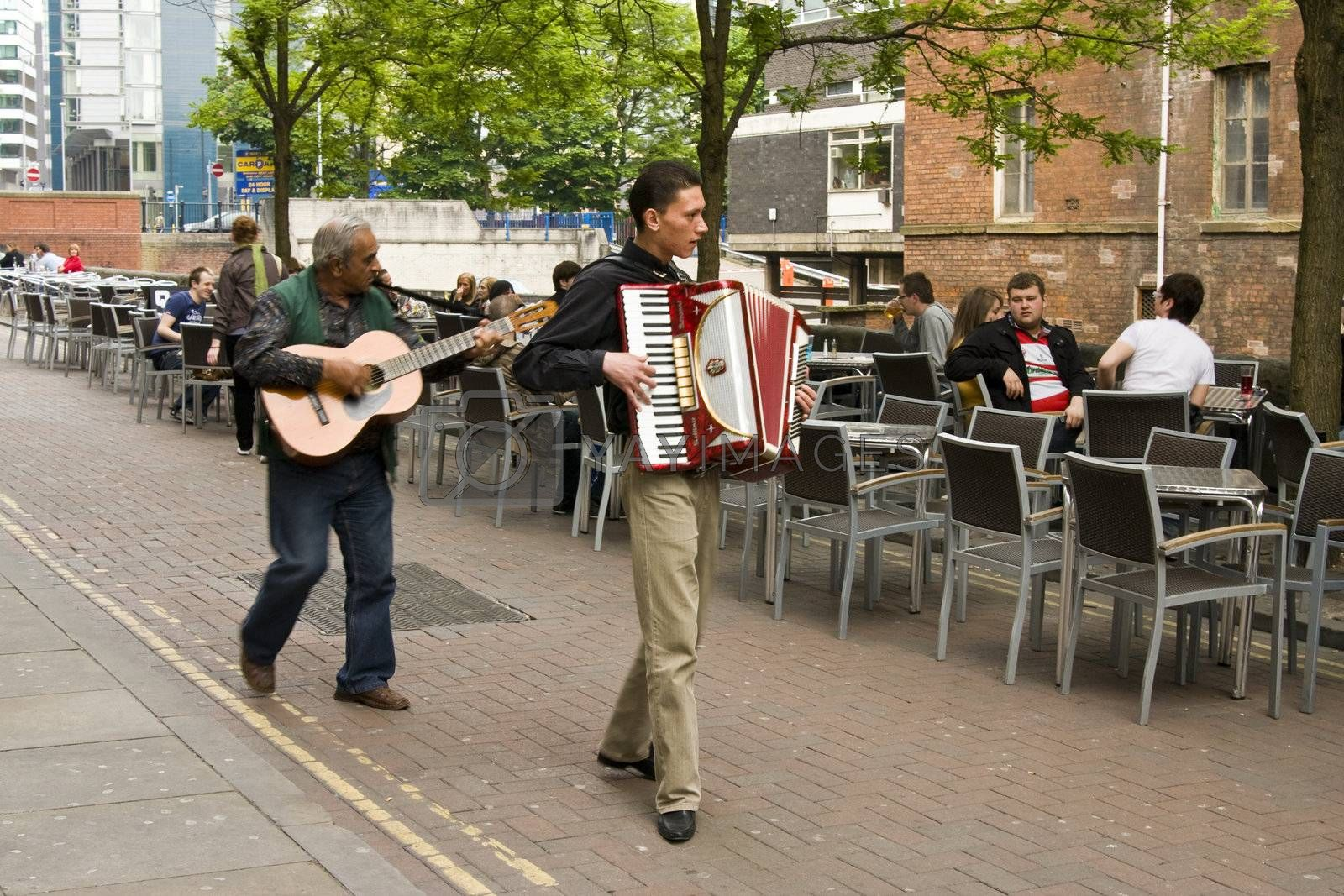 two Gipsy street performers playing guitar and accordion on canal street , Manchester, UK