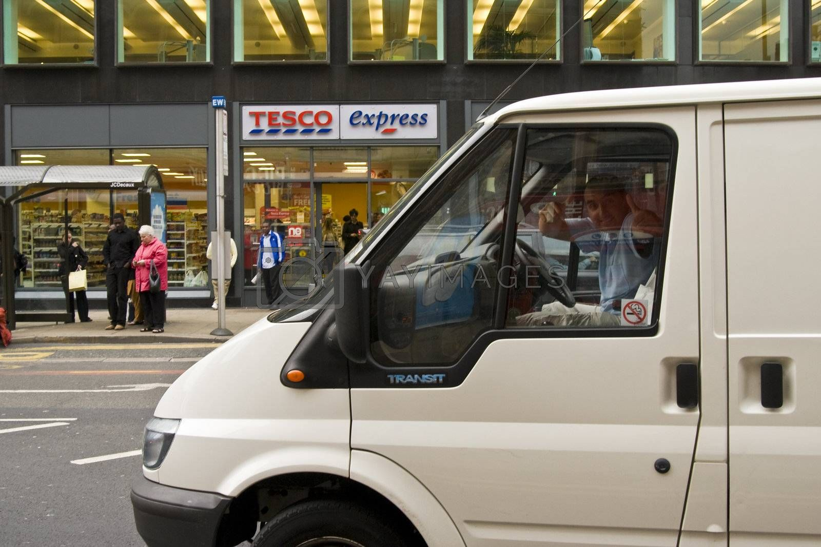 Thumbs up from man in delivery van in fron of Tesco express on London Road in Manchester city center
