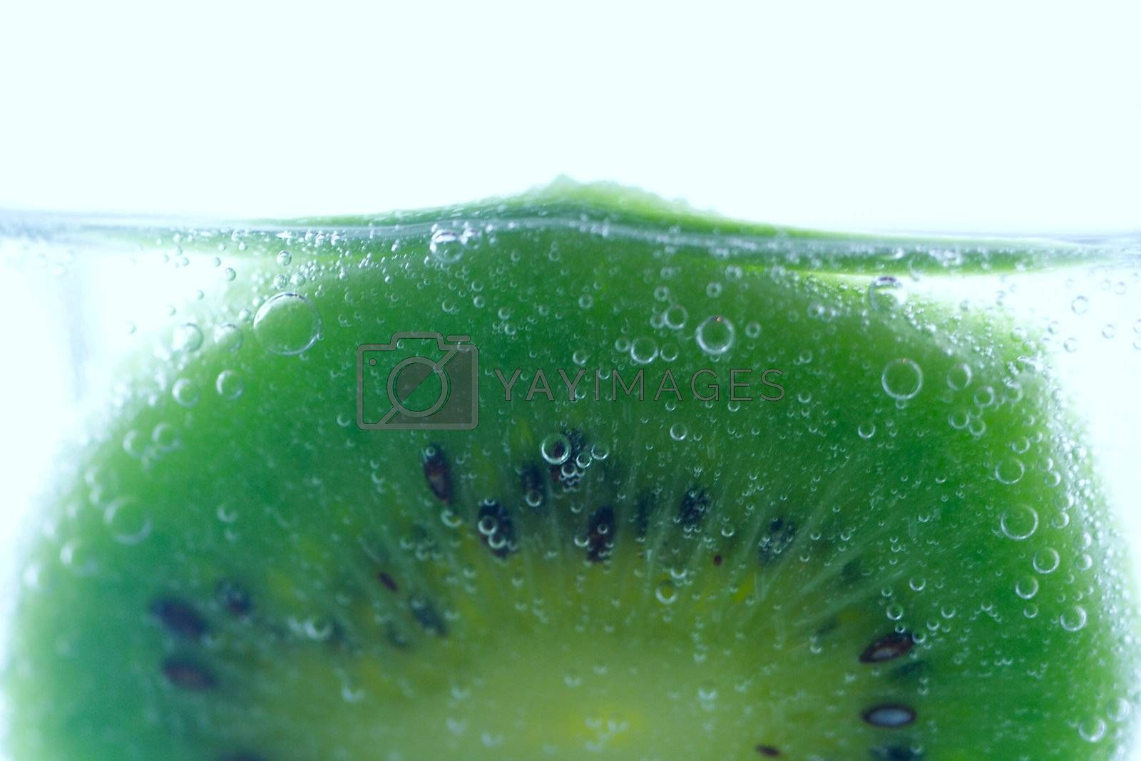 close-up slice of kiwi in water with bubbles