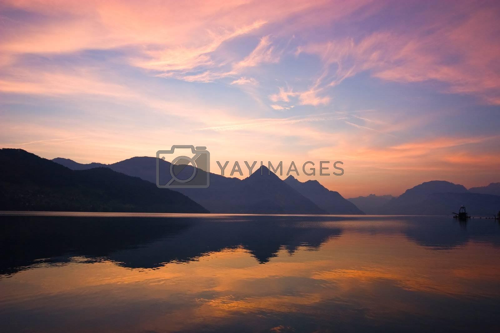 Beautiful sunrise over mountains, reflected on lake. Central Switzerland.