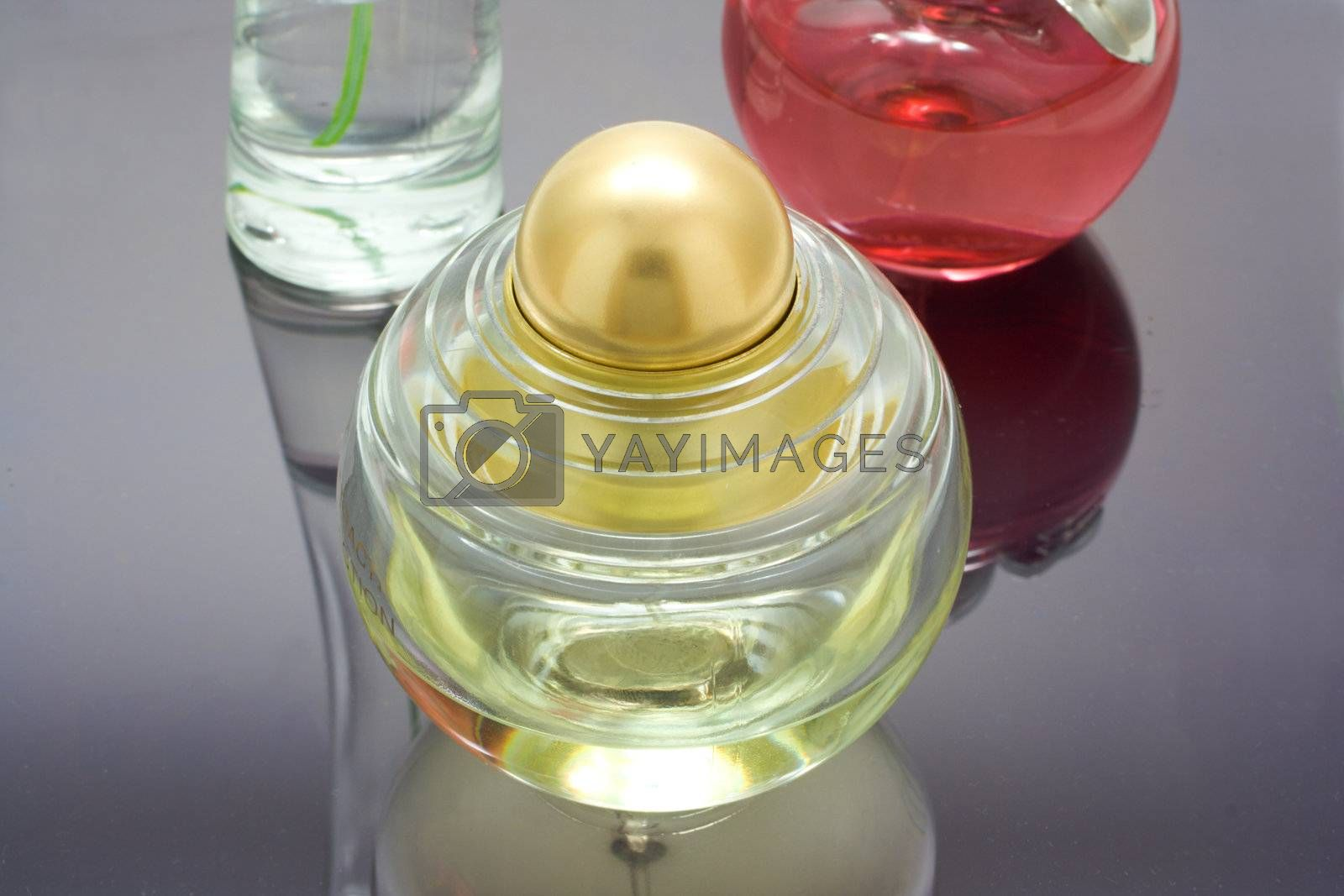 three bottles of perfume on mirror table