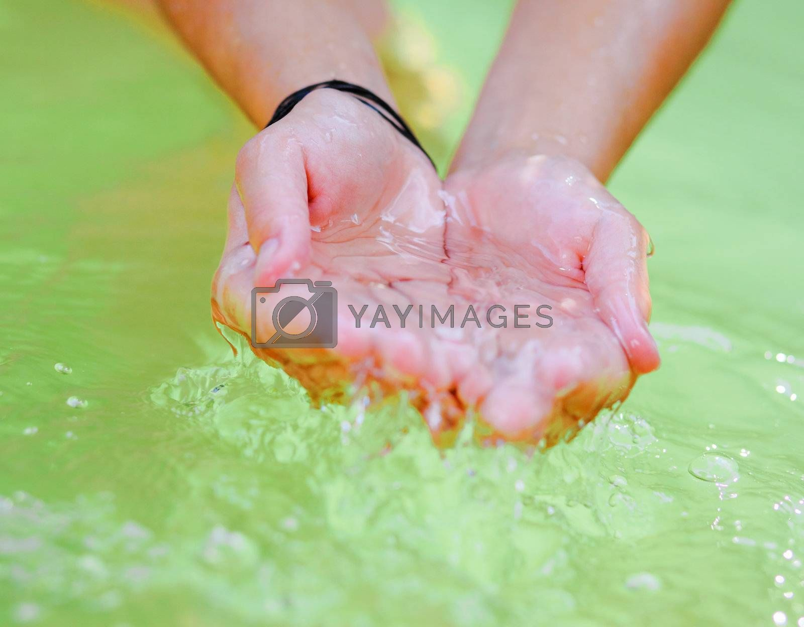 Woman's hands playing with fresh water