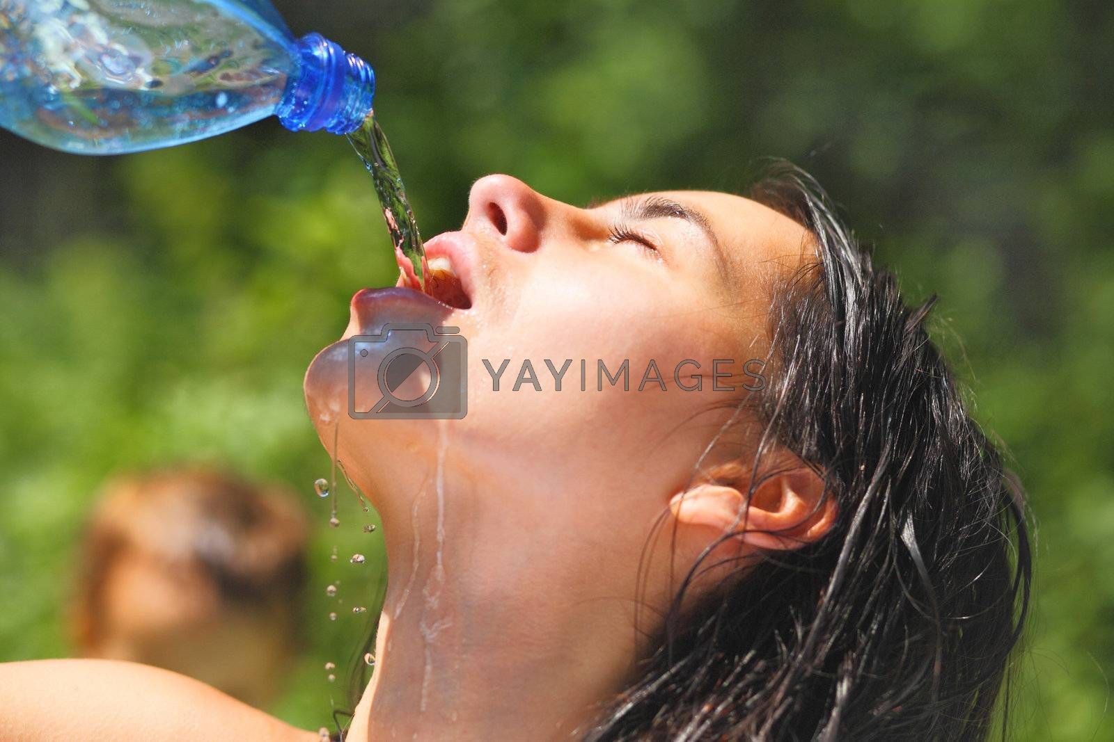 Young woman drinking water outdoors. She has a thirst