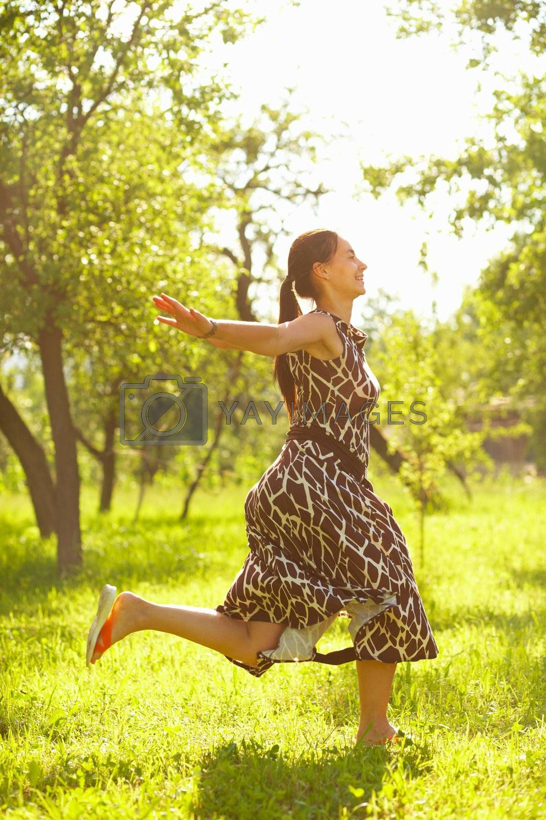 Young beautiful woman jumping in a meadow