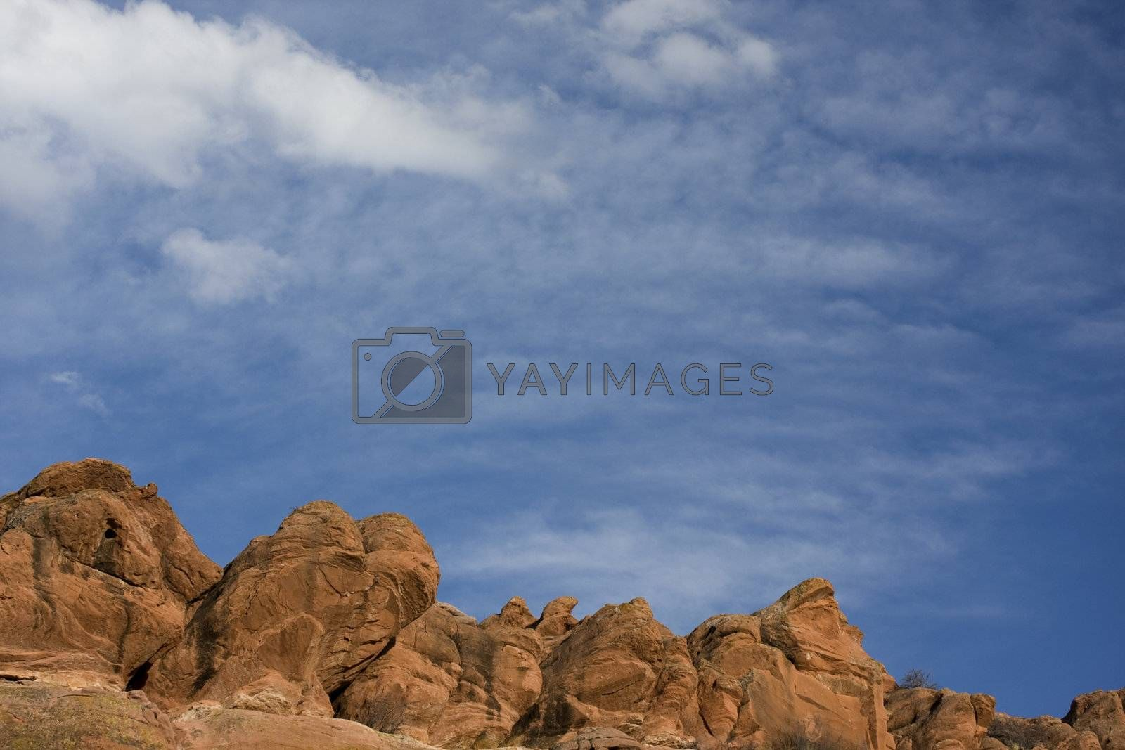 red sandstone rocks, blue sky with delicate white cumulus and cirrocumulus clouds at foothills of Rocky Mountains in Colorado