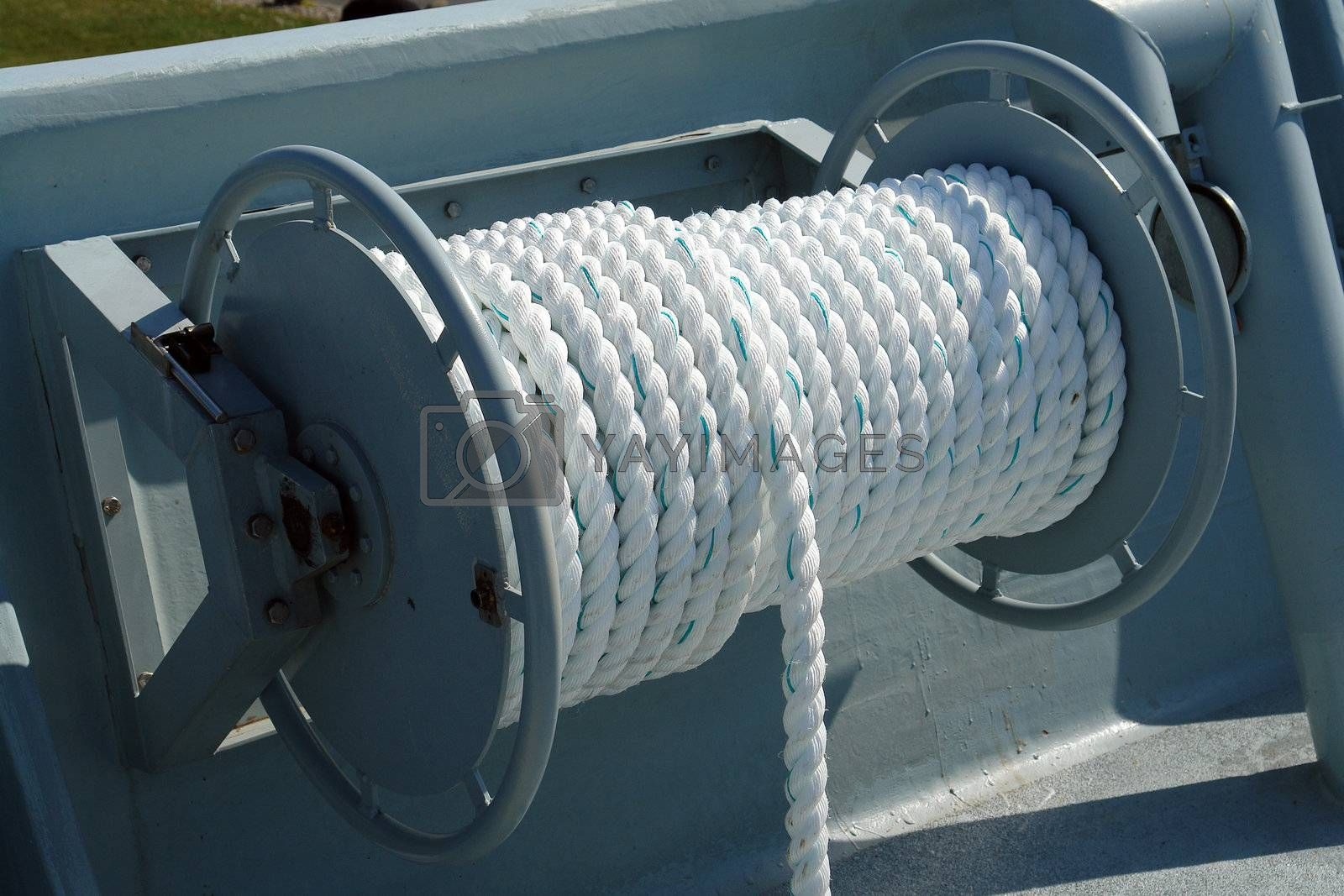 Nautical boat rope rolled on a metal drum winch on deck