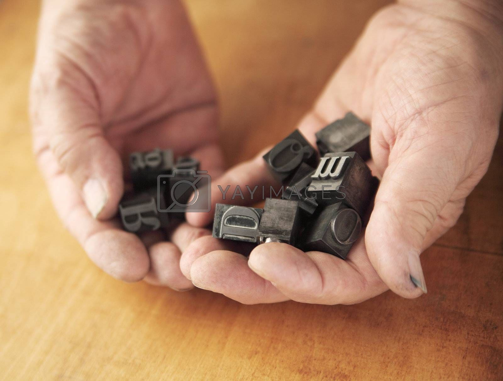 printer's ink-stained hands holding metal type pieces